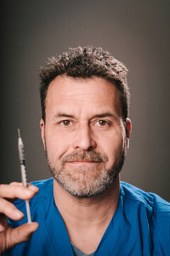 Mature doctor with syringe in front of gray background