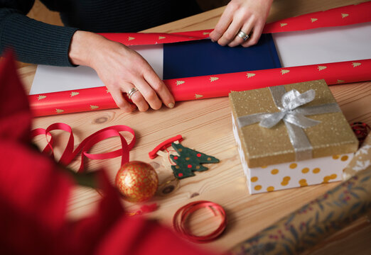 Woman wrapping gift by during Christmas on table