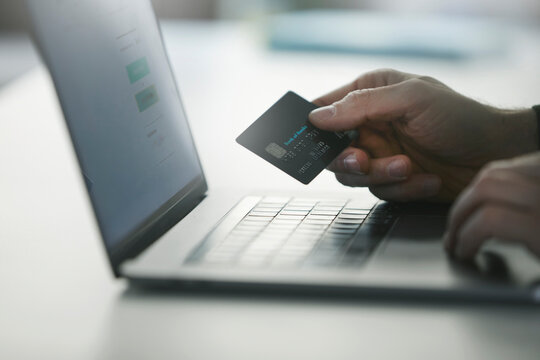Man making online payment through credit card on laptop