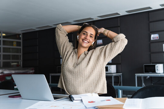 Smiling businesswoman with hands behind head sitting at desk in office