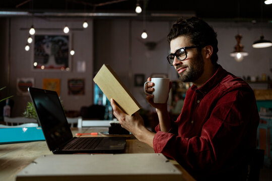 Smiling male freelancer with laptop reading book while having coffee in cafe