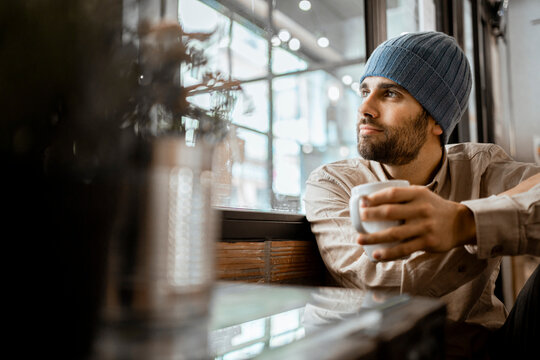 Mid adult man wearing knit hat with coffee cup looking through window in cafe