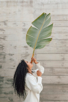 Curly haired woman holding big banana leaf by wall