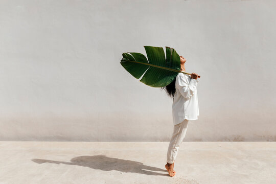 Young woman carrying big leaf on shoulder while standing on tiptoes by white wall during sunny day