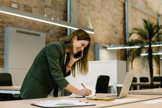 Cheerful businesswoman talking on smart phone while writing in diary by laptop at office