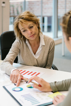 Mature businesswoman explaining graph to female coworker at desk in coworking office