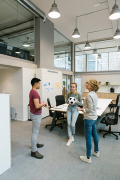 Male and female entrepreneurs playing soccer ball in coworking office