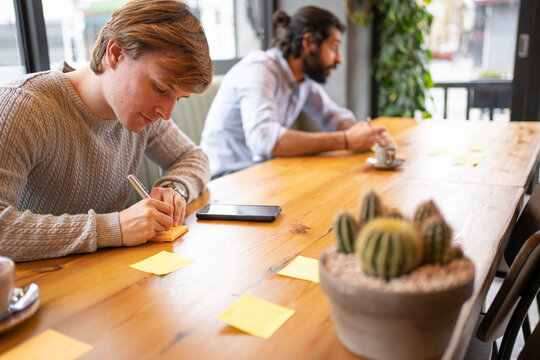 Young businessman writing strategy while sitting at desk in office