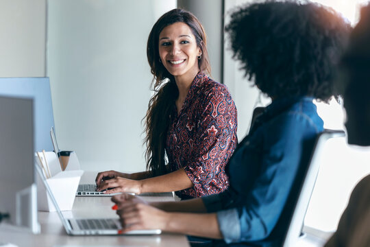 Smiling female professional looking at colleague while working on laptop in office