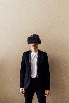 Young professional using virtual reality simulator in front of wall in office