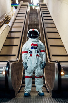 Mid adult astronaut standing in front of escalator