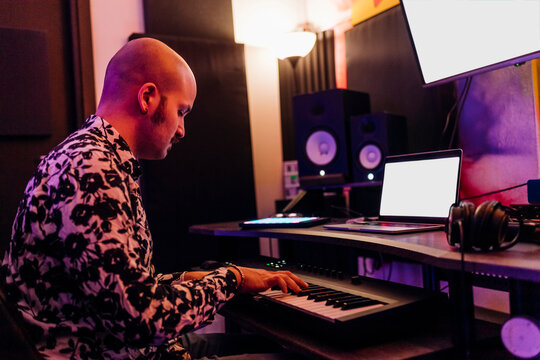 Man playing piano while composing music in studio