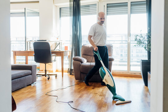 Mustache man cleaning floor with vacuum cleaner at home