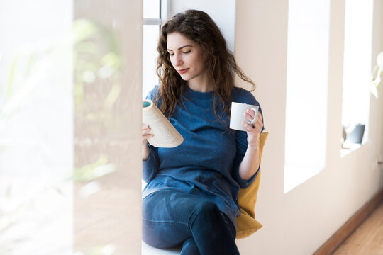 Beautiful woman reading book while having coffee at window in living room