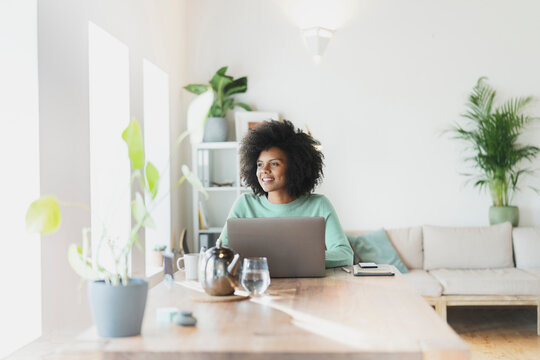 Smiling woman with laptop looking away at home