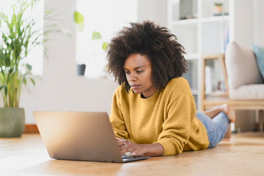 Woman using laptop while lying on floor at home