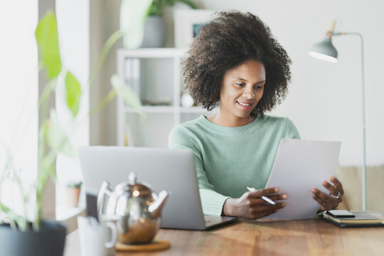 Smiling woman checking document while working at home