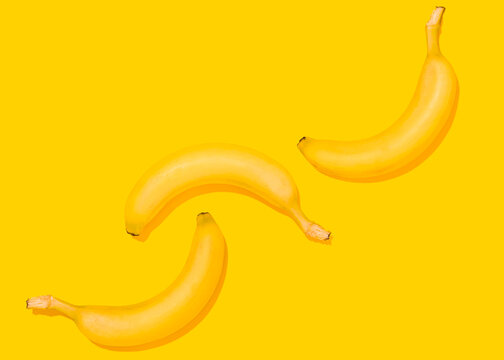 Studio shot of three bananas lying against yellow background