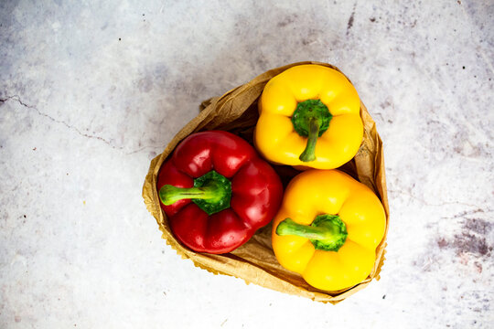 Studio shot of paper bag with single red and two yellow bell peppers