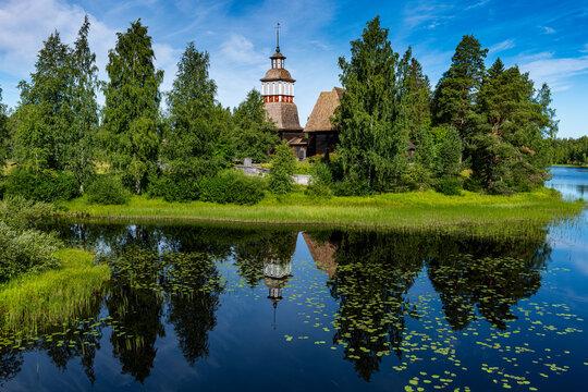Wooden church reflecting in shiny lake