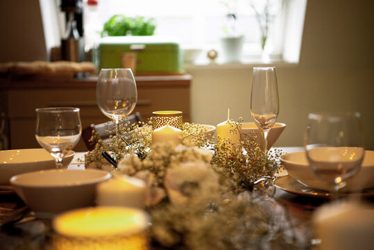 Bowl and wineglasses with flowers arranged on dining table at home