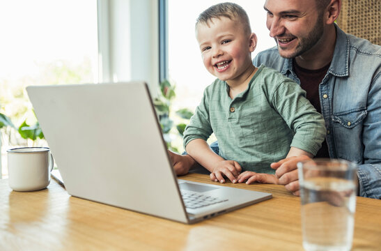 Cheerful son and father sitting with laptop doing video call at home