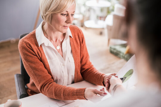 Businesswoman discussing with female colleague over graph data in home office