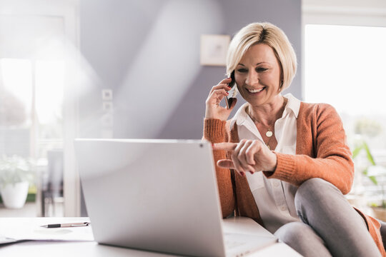 Smiling female professional pointing at laptop while communicating through smart phone at home