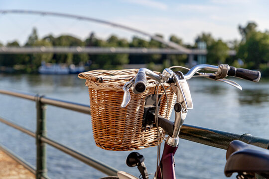 Selective focus of handlebar and wicker baskets of bicycle parked along the Meuse river with blurred view of the Hoge brug (high bridge) as background in Maastricht, Netherlands.
