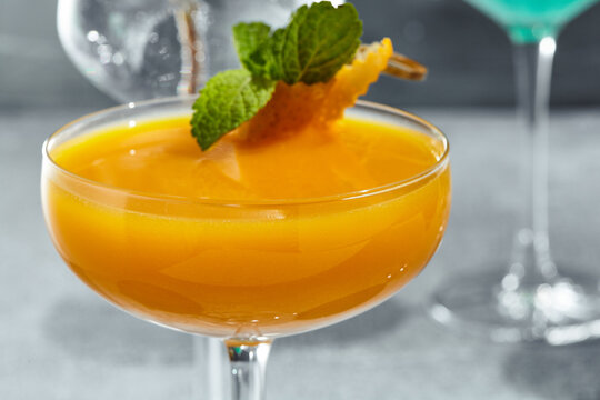 Cocktail with vodka and mango. Summer day cocktail concept with sunlight and shadow. Cocktail garnished with mint leaf and orange peel.