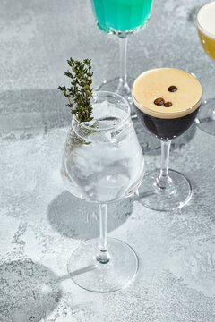 Cocktail with vodka and thyme. Summer day cocktail concept with sunlight and shadow. Cocktail in wine glass.