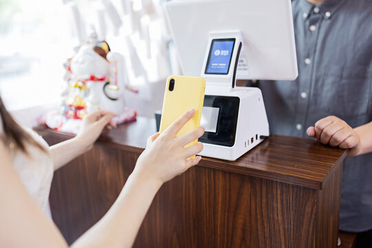 cashier using digital device for payment. Man waiter calculates young woman in cafe by mobile phone via QR code of Alipay or Wechat pay (popular payment metod in China). The concept of the restaurant