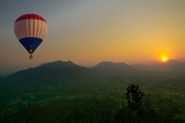 Hot air balloon flying over the mountain with scenic view of sunset in background in Northeast Thailand.