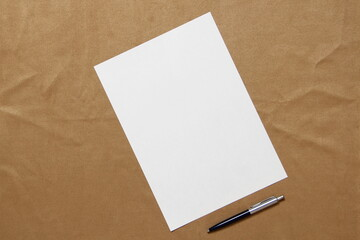 Obraz Template of white paper with pen lies diagonally on light brown cloth background. Concept of business plan and strategy. Stock photo with empty space for text and design. - fototapety do salonu