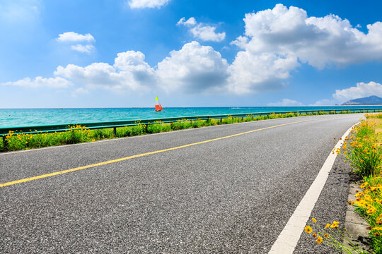 Empty asphalt road and sea natural landscape under blue sky.