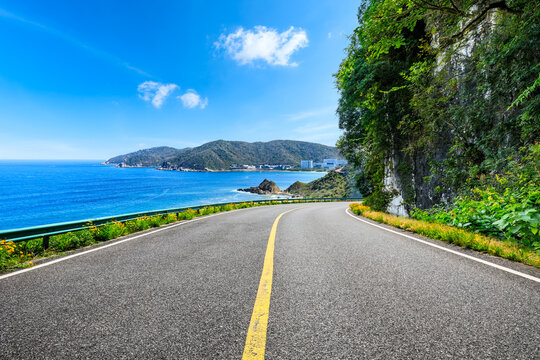 Asphalt highway and mountain with blue sea natural landscape.
