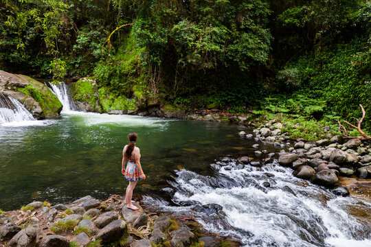 Young australian Caucasian woman at the edge of a peaceful river pool in forest