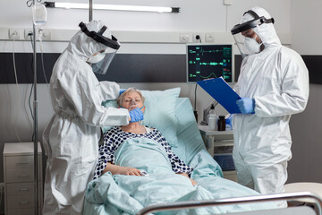 Medical team in clinic wearing coverall ppe and face shield during patient visit in hospital room in time of coronavirus out break to prevent infection. Uconscious senior woman breathing with help - fototapety na wymiar