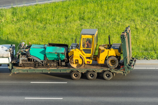 Transporting the road roller and asphalt paver on the cargo platform by the truck trailer.
