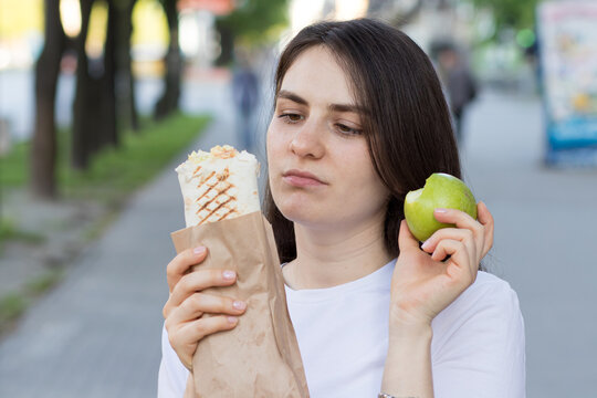 Young beautiful brunette woman on a diet chooses food - what to eat an apple or fast food.
