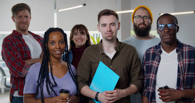 Happy diverse team standing together at creative office and looking at camera