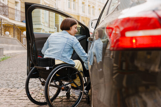 Brunette woman in wheelchair getting into car on city street