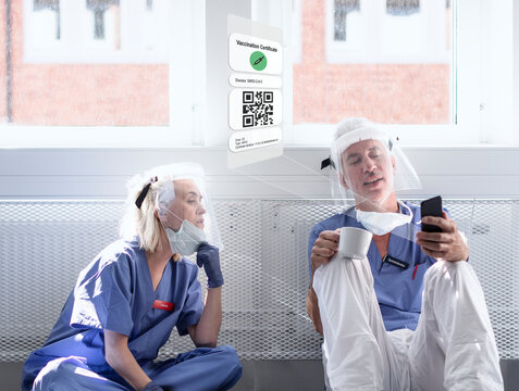 Doctors wearing personal protective equipment looking at cell phone with Covid-19 vaccine certificate