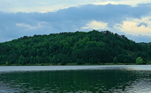 Beautiful mountain across a lake in the Chattahoochee National Forest with clouds in the sky at Rocky Mountain State park in Georgia