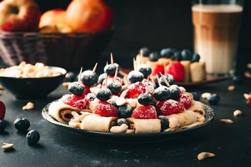 Obraz Breakfast pancake. A healthy breakfast with fruit. Pancake with fruit. Iced coffee and fruit. Dark background with pancakes and fruit. - fototapety do salonu