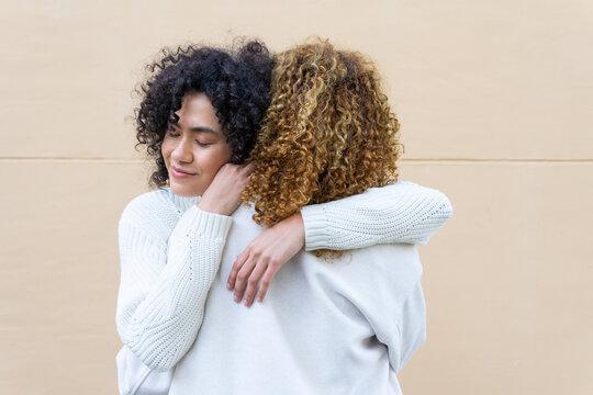 Loving woman embracing girlfriend on street