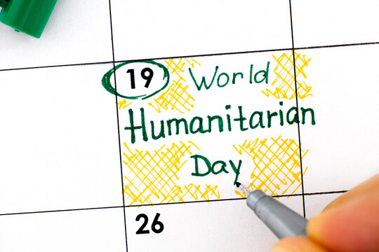 Woman fingers with pen writing reminder World Humanitarian Day in calendar.