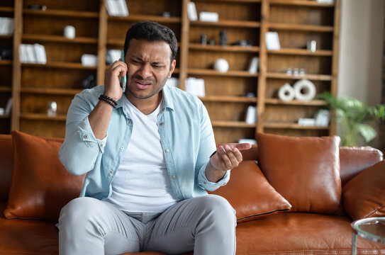 Angry stressed indian man has unpleasant phone conversation, talks on the smartphone and arguing, sits on the sofa and speaking with frustrated face expression