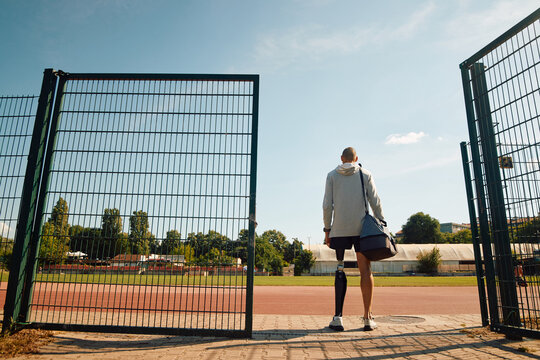 Rear view of disabled athlete with artificial leg standing at entrance gate at the stadium.