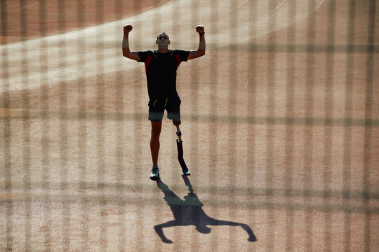 Disabled athlete with leg prosthesis celebrating success while standing at the stadium with his arms raised.